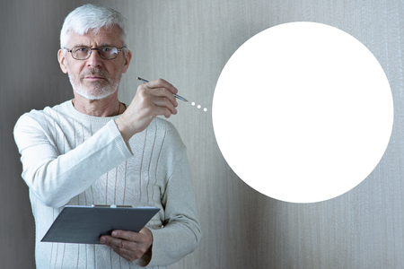 a gray-haired man in light clothes and glasses enters into a contract on paper Banco de Imagens