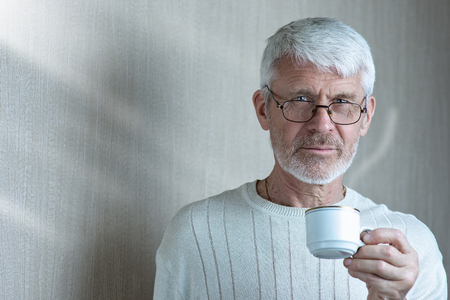 portrait of a gray-haired man holding a Cup of coffee