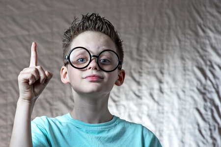 a boy in a light t-shirt and round glasses raised his index finger he had an idea