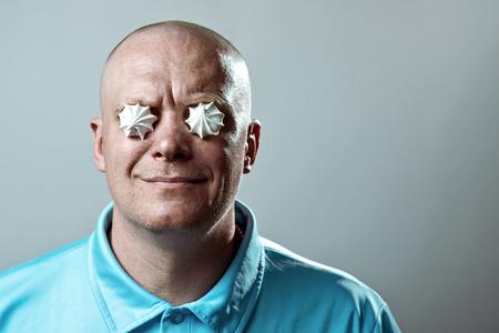 a bald brutal man in a blue t-shirt put meringues in his eyes Stok Fotoğraf