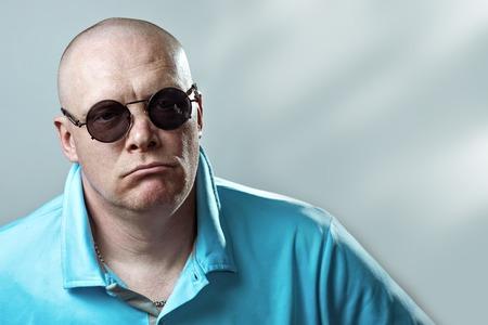 hombre brutal calvo con gafas redondas y una camiseta ligera tira de una cadena de plata