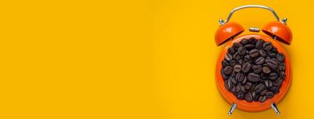 coffee beans in orange alarm clock on bright yellow background Фото со стока