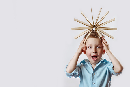 the surprised boy in a blue shirt and drive on her head on bright background