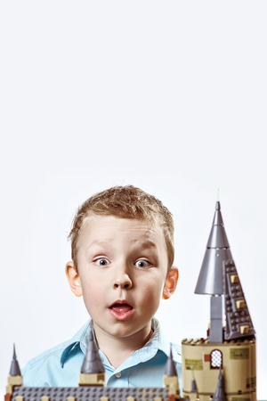 the surprised boy in a light shirt looks out from the constructed lock of the designer on a light background Stock Photo