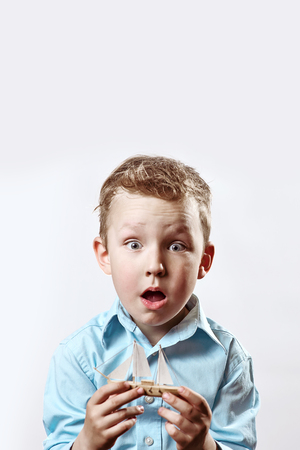 surprised boy in a blue shirt holding a boat in his hands on a light background Stock Photo