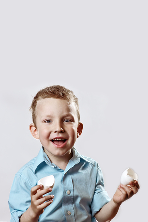 cheerful boy in a light shirt holding a shell from the egg and smiling on a light background