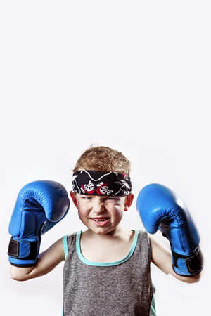 fighting emotional boy in Boxing gloves and bandana on light background Stock Photo