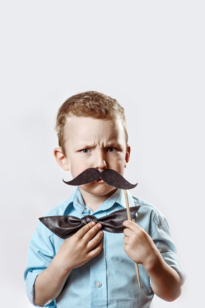 a frowning serious boy in a light shirt put a mustache on a stick and a bow tie on his face to make him look older. Stock Photo