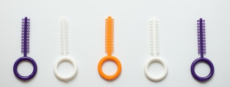 a multi-colored orthodontic ligatures for alignment of the orthodontists teeth on a light background Stock Photo