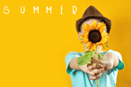 a summer boy in a light t-shirt with a yellow sunflower covers his face