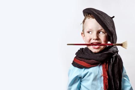 Junge Künstler in schwarzer Baskenmütze, Schal und mit einem Pinsel im Mund auf hellem Hintergrund