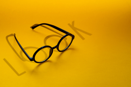 black round glasses on a yellow background with hard shadow and the inscription look