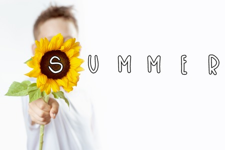 summer boy in a light t-shirt with a yellow sunflower covers his face