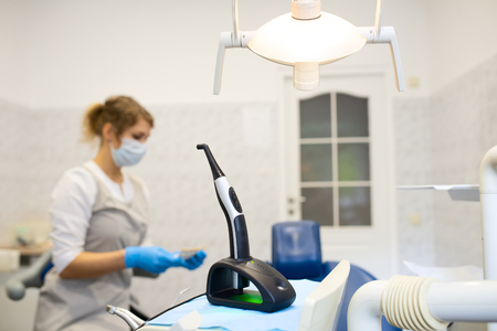 modern photopolymerization lamp for light fillings in the dental office, on a blurred background Stock Photo - 124752663