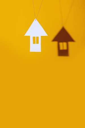 a small house made of cardboard casts a shadow on a bright colored background