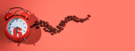 coffee beans in orange alarm clock on bright pink background