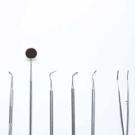 various dental tools laid out flatlay on a light background