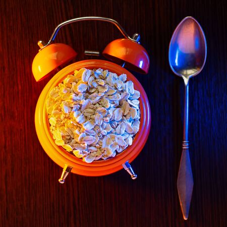 Concept on the topic of Wake up its morning. Oatmeal in an orange alarm clock, and next to the spoon. Stock Photo