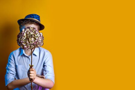 a man in a hat holding a bouquet in front of his face on a bright colored background Stock Photo
