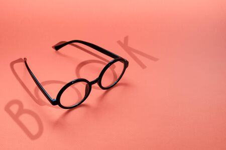 black round glasses on a pink background with a hard shadow and the inscription book