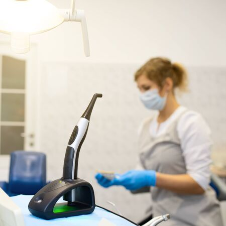modern photopolymerization lamp for light fillings in the dental office, on a blurred background