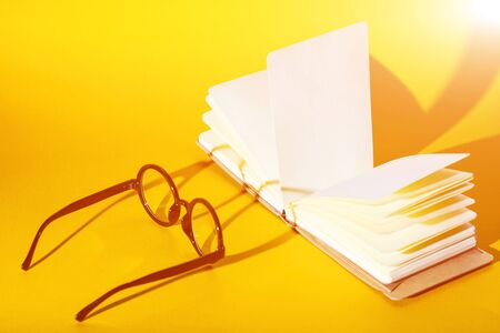 black round glasses on a yellow background with a hard shadow and the inscription look Stock Photo