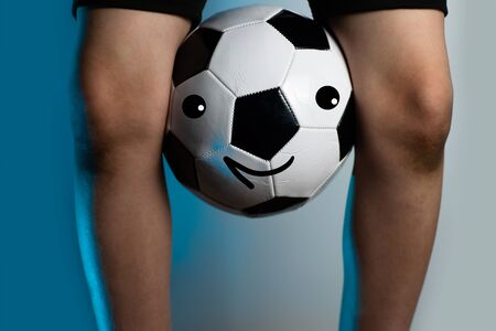 football goalkeeper with dirty knees clamped the ball between his legs on a blue background