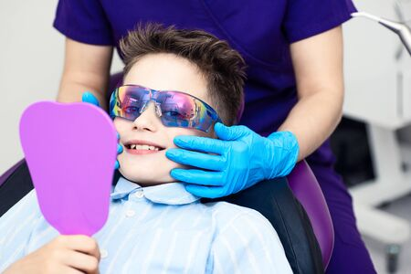 the boy in special glasses in the dentist's chair. the doctor in sterile gloves shows him his smile in the mirror. Banque d'images