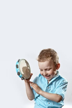 cheerful boy in a blue shirt holding a tambourine and smiling on a light background Banque d'images