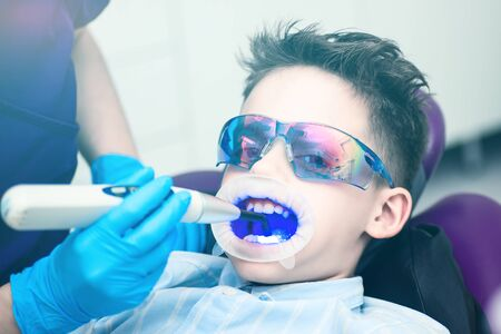 The boy with goggles in the dental chair. Mouth directed lightpolymerization lamp with blue light for sustainable fillings.