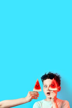 boy in a light t-shirt watermelon on a stick closes one eye on a blue background Banco de Imagens
