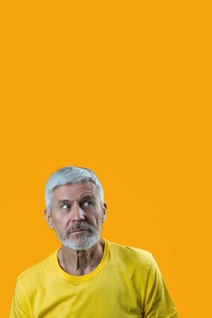 portrait of a surprised and curious gray-haired man with a beard on a yellow background