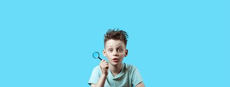 a boy in a light t-shirt holding a small magnifying glass on a blue background 免版税图像