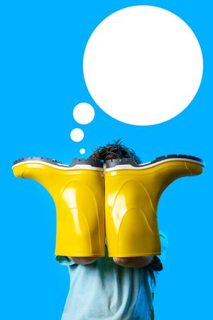 a boy in a light t-shirt covered his face with yellow rubber boots. symbolizes autumn on a blue background