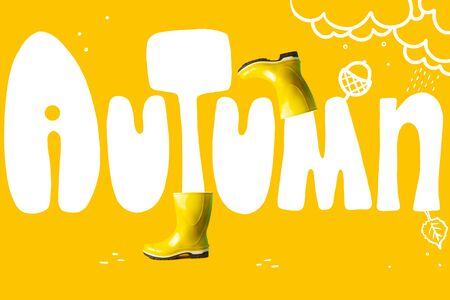 The inscription autumn in large letters on a colored background. As well as yellow rubber boots and tree leaves