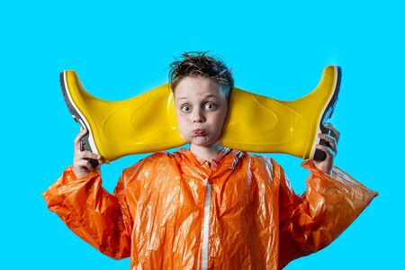funny boy in an orange coat with puffed-out cheeks and rubber boots on a blue background Stock Photo