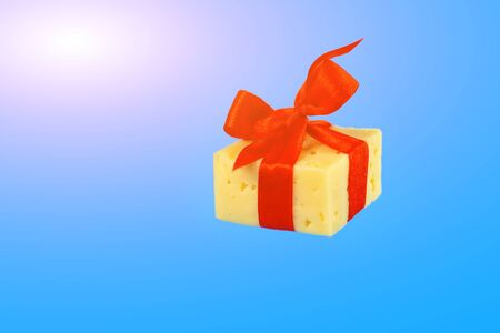 floating in the air gift of cheese tied with a red ribbon on new year rats on a blue background Stock Photo