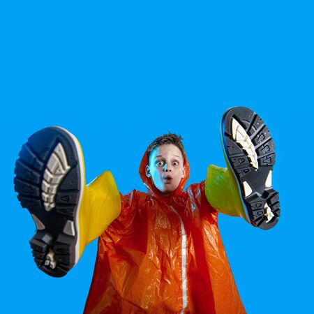 smiling boy in orange raincoat stuck his hands in rubber boots on a blue background