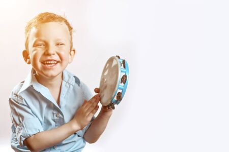 cheerful boy in a blue shirt holding a tambourine and smiling on a light background Stock Photo
