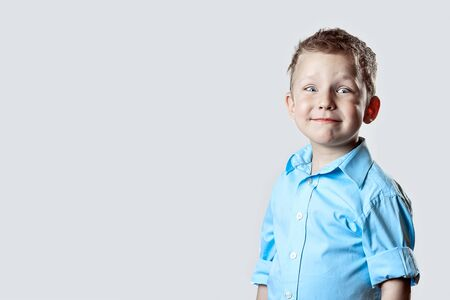 smiling happy boy in blue shirt on light background