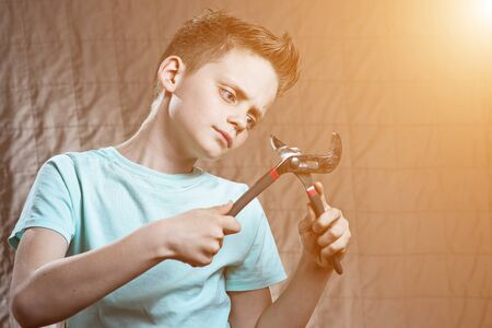 a boy with a wrench and surprised eyes repairs something Stock Photo