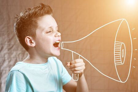 a boy painted with a loudspeaker shouting at him Stock Photo