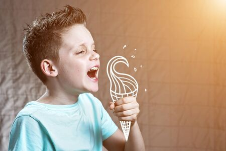 a boy in a light t-shirt eating painted ice cream from which flying spray