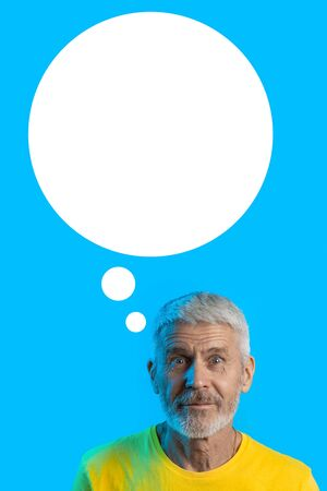 portrait of surprised and curious gray-haired man with a beard on a blue background