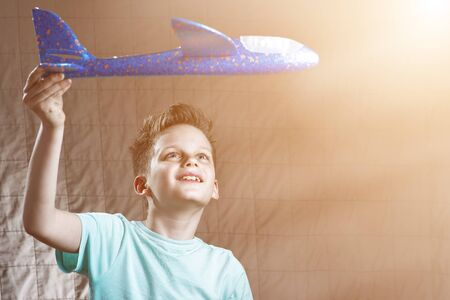 boy launches blue model airplane and dreams of flying