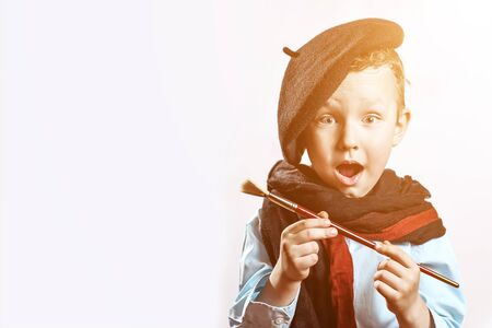 boy artist in black beret, scarf and with a brush in his mouth on a light background Stock Photo