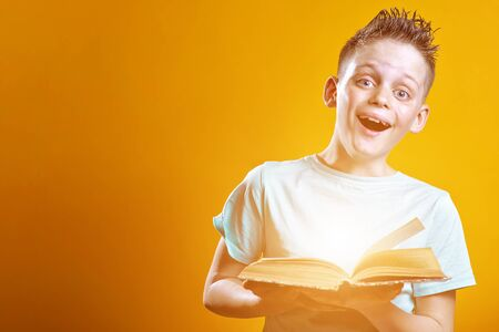 cheerful boy in a light t-shirt holding a book on a colored background Stock Photo