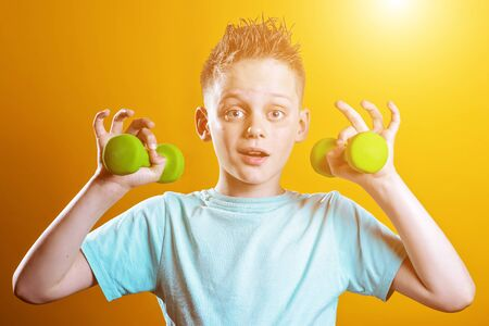 a boy in a bright t-shirt with dumbbells on a yellow background Zdjęcie Seryjne