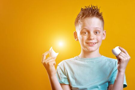 cheerful boy in a light t-shirt holding a broken egg on a colored background