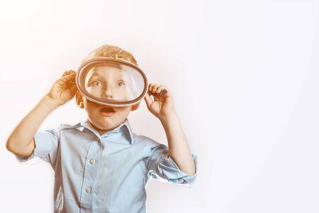 een verraste jongen in een blauw shirt met een onderwatermasker om op een lichte achtergrond te zwemmen